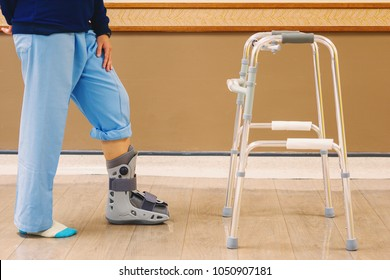 In the hospital, patients suffered from fracture of the ankle, needing to wear an orthopedic boot, and practice walking with Walker to maintain the balance. medical and orthopedic concept.