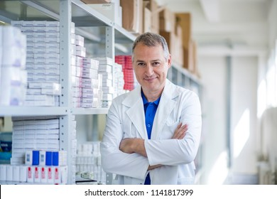 Hospital pharmacist worker. Portrait of cheerful smiling male pharmacist in pharmacy drugstore. Male pharmacists working in warehouse depot. Mature Pharmacist posing chemist's shop