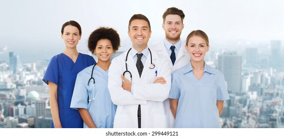 hospital, profession, people and medicine concept - group of happy doctors over city background