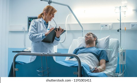 In the Hospital Professional Female Doctor Asks Questions to the Patient and Writes Answers in the Medical Chart. Clean and Modern Medical Ward.