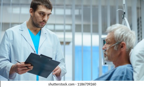 In the Hospital, Recovering Senior Patient Lying in Bed Talks with a Friendly Doctor. Professional Doctor Asks Patient Vital Questions in the Modern Geriatrics Ward.