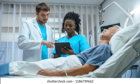 In the Hospital, Senior Man Sleeps in the Bed, Doctor and Nurse Standing in the Ward, Using Tablet Computer. Technology Helps Cure Patients, Modern Hospital Ward.