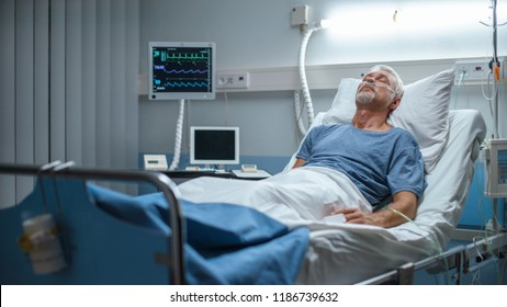 In the Hospital Senior Patient Rests, Lying on the Bed. Recovering Man Sleeping in the Modern Hospital Ward.