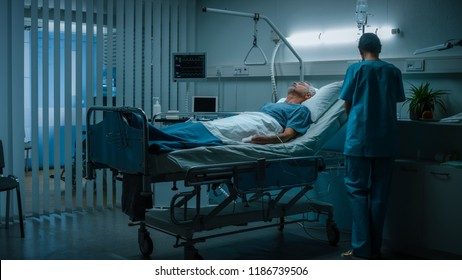 In the Hospital Senior Patient Rests on the Bed, Nurse in Ward Does Checkup. Recovering Man Sleeping in the Modern Hospital Ward.