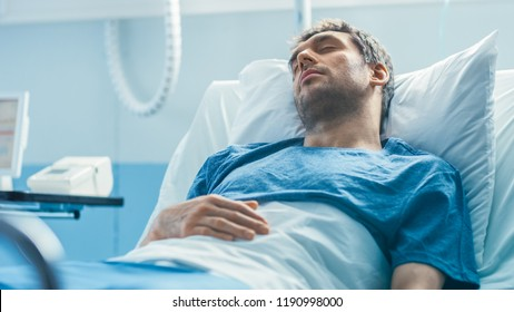 In the Hospital Sick Male Patient Lies on a Bed Sleeping, Heart Rate Monitor On His Finger. Bright and Modern Medical Ward.