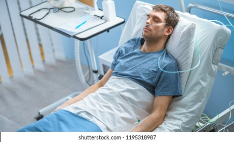 In the Hospital Sick Male Patient Sleeps on the Bed, He's Wearing Nasal Cannula to Help Him Breath. Terminally Ill Man in a Come.