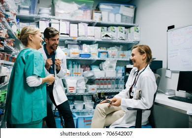 Hospital staff having casual discussion in the pharmacy. Three colleagues meeting in drugstore and laughing.