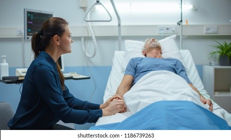 In the Hospital Ward Recovering Father is Visited by Daughter. Senior Sick Man Sleeping in Bed Daughter Sits Beside, Worrying. Modern Private Ward. Family Values.