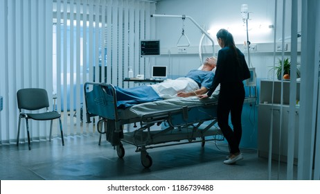 In the Hospital Ward Recovering Father is Visited by Daughter. Senior Sick Man Sleeping in Bed Daughter Stands Beside, Worrying. Modern Private Ward. Family Values.