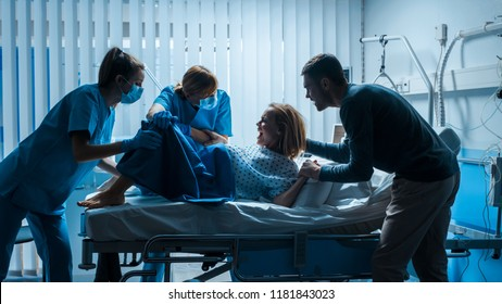 In the Hospital Woman in Labor Pushes to Give Birth, Obstetricians Assisting, Husband Holds Her Hand for Support. Modern Maternity Ward with Professional Midwives. Side View Footage.