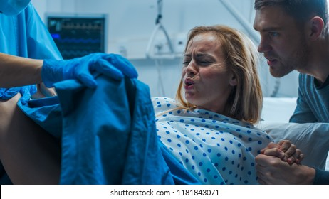 In the Hospital Woman in Labor Pushes to Give Birth, Obstetricians Assisting, Husband Holds Her Hand for Support. Modern Delivery Ward with Professional Midwives.