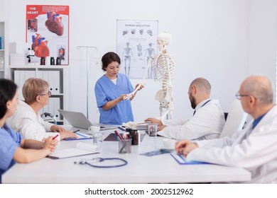 Hospital woman nurse presting bone structure using body anatomy skeleton discussing medical expertise. Physician team working in meeting room at healthcare treatment explaining health diagnosis - Shutterstock ID 2002512962
