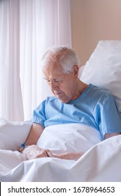 Hospitalized elderly man, sitting in the room.