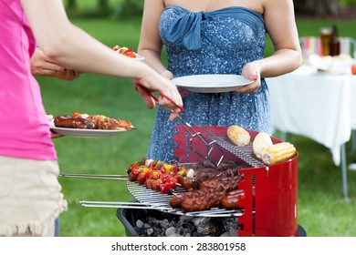 Host serving grilled meals on barbecue party