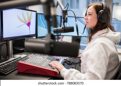 Host Using Headphones And Microphone While Looking At Monitor
