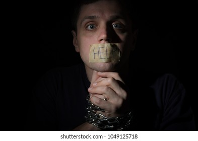 Hostage chained in a chain praying for help with an inscription help on an adhesive tape on the mouth isolated on a black background
