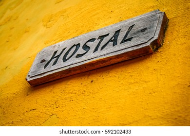Hostal sign in yellow wall