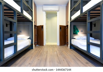 Hostel, hotel, dormitory beds on wooden floor with dim lighting. Accomodation for travelers. Clean and modern design. Bedroom with air condition.