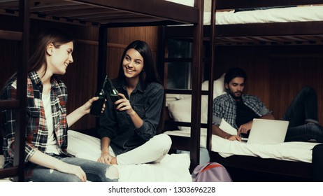 Hostel for Young People. Best Friends Traveling. Small Room in Hostel. spend time Together. bunk beds in room. sit on bed. looking on each other. holding bottles. girls smiling. cheers
