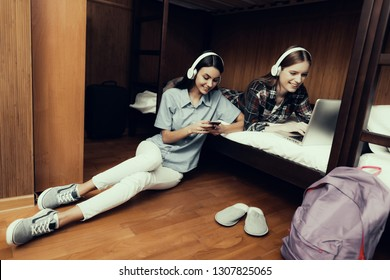 Hostel for Young People. Best Friends Traveling. Small Room in Hostel. spend time Together. bunk beds. smiling Woman. looking at laptop and phone. girls on bed. listen to music. sitting on floor
