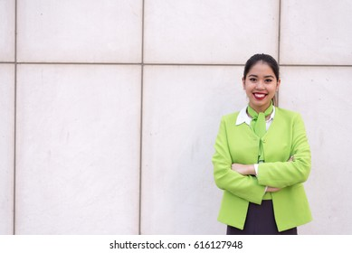 hostess woman or stewardess smiling crossed arms green
