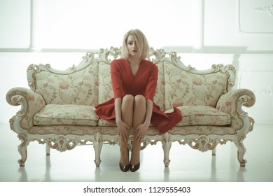 hostess woman welcome guests. hostess job searching. hotel reception hostess sit on sofa in red dress. hostess.