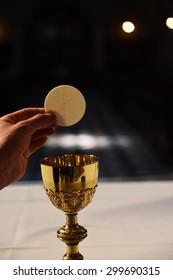 Hostie held over golden chalice.