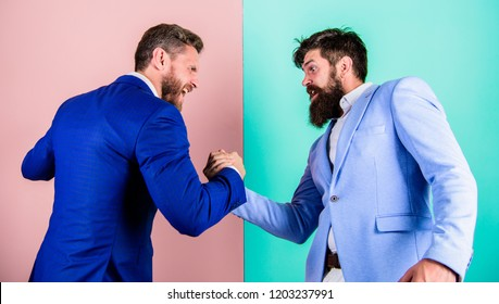 Hostile or argumentative situation between opposing colleagues. Business partners competitors office colleagues tense faces ready to compete in arm wrestling. Business competition and confrontation.