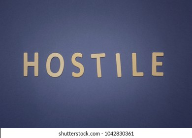 Hostile written with wooden letters on a blue background to mean a business concept