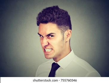 Hostile young business man looking at camera with angry face expression