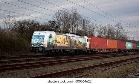 Hostka, Czech Republic - March 14, 2017 - Modern silver electric locomotive 386 020-2 with graphic design Hamburg, 150 Jahre Hafenbahn, Metrans, HHLA, in the head of freight (cargo) container train.