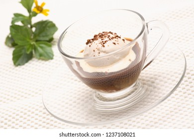Hot Affogato coffy in a clear glass on a white background with coffee beans.