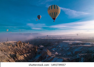 Hot air ballons flying over Cappadocia National Park Göreme Turkey, fogyy air