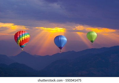 hot air ballons over mountain with ray of sunrise in background