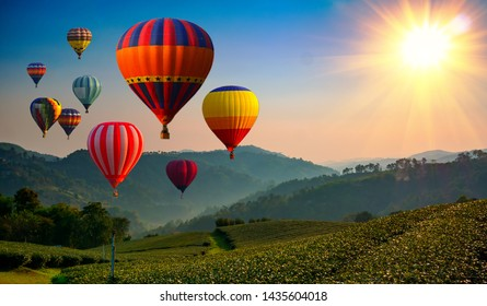 Hot air balloon above high mountain at sunrise or sunset.