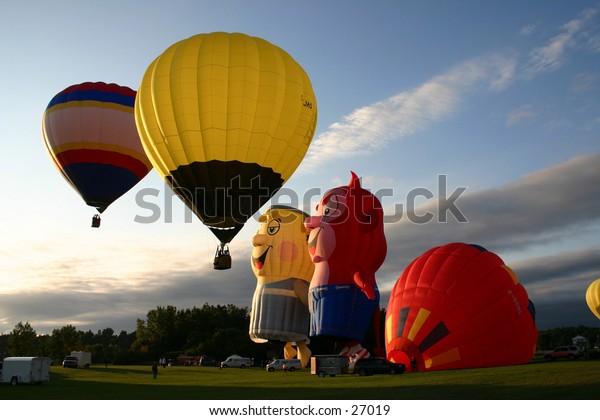 Hot air balloon alighting at sunrise