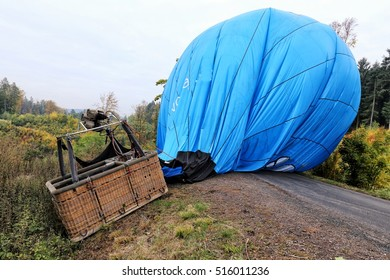 Hot air balloon basked and envelope laid over the road by forest