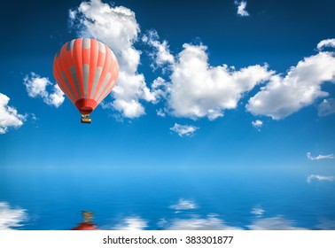 hot air balloon in blue sky over water surface