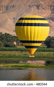 A hot air balloon carrying tourists over the River Nile at Luxor with the Theban Hills in the background