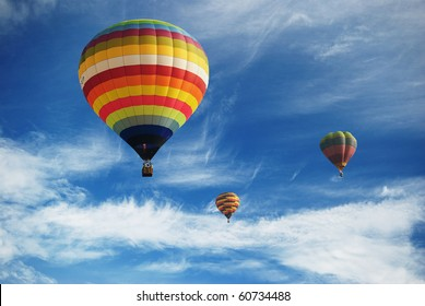 Hot air balloon in the cloudy blue sky