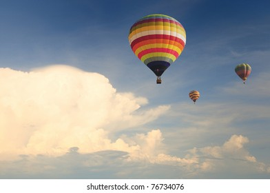 Hot air balloon in the cloudy blue sky during sunset