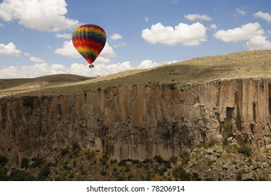 Hot air balloon in cloudy sky over the rocks