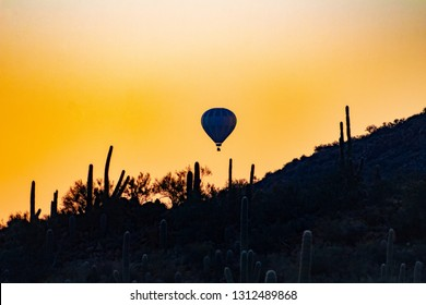 A hot air balloon drifting over silhouettes of cacti in the early dawn light just before sunrise. Saguaro Cactus and trees, warm skies, a ballooning adventure in the Sonoran Desert. Tucson, Arizona.