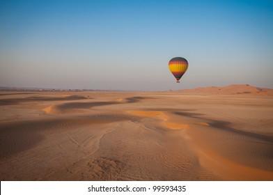 Hot Air Balloon floating over the desert sand