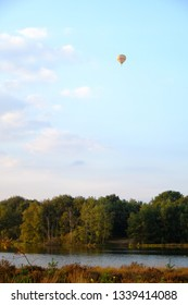 Hot air balloon flying in the distance over a forest lake against a dusk and setting sun sky