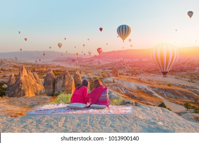 Hot air balloon flying over spectacular Cappadocia - Girls watching hot air balloon at the hill of Cappadocia