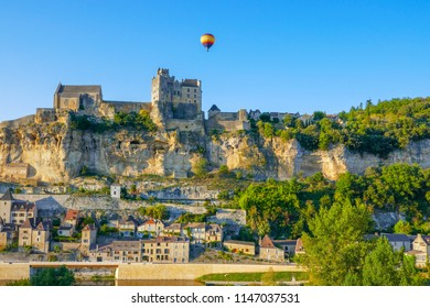 Hot air balloon flying over Beynac Chateau in the Dordogne