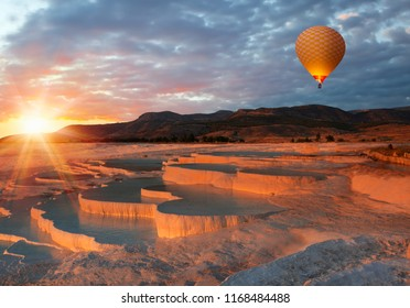 Hot air balloon flying over spectacular PAmukkale - Natural travertine pools and terraces in Pamukkale - Cotton castle in southwestern Turkey