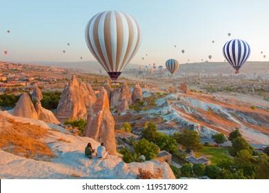 Hot air balloon flying over spectacular Cappadocia - A Couple watching the hot air balloon at the hill of Cappadocia