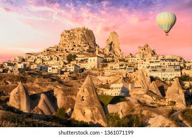 Hot air balloon is flying over Cappadocia near Uchisar castle at beautiful dramatic sunrise, Turkey